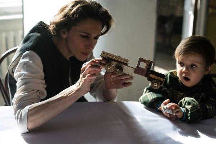 Ольга с ребенком играют с картонным грузовиком